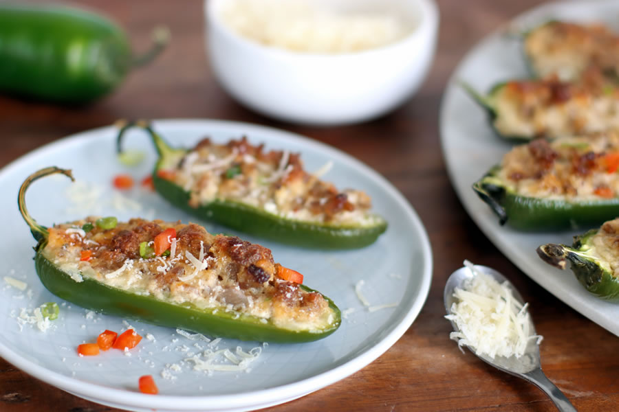 2 baked jalapenos with sausage, cream cheese, asiago and parmesan cheese on a plate